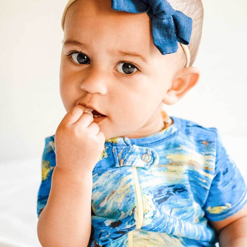 Baby wearing a short sleeve romper with a print of Vincent van Gogh's famed painting, The Starry Night