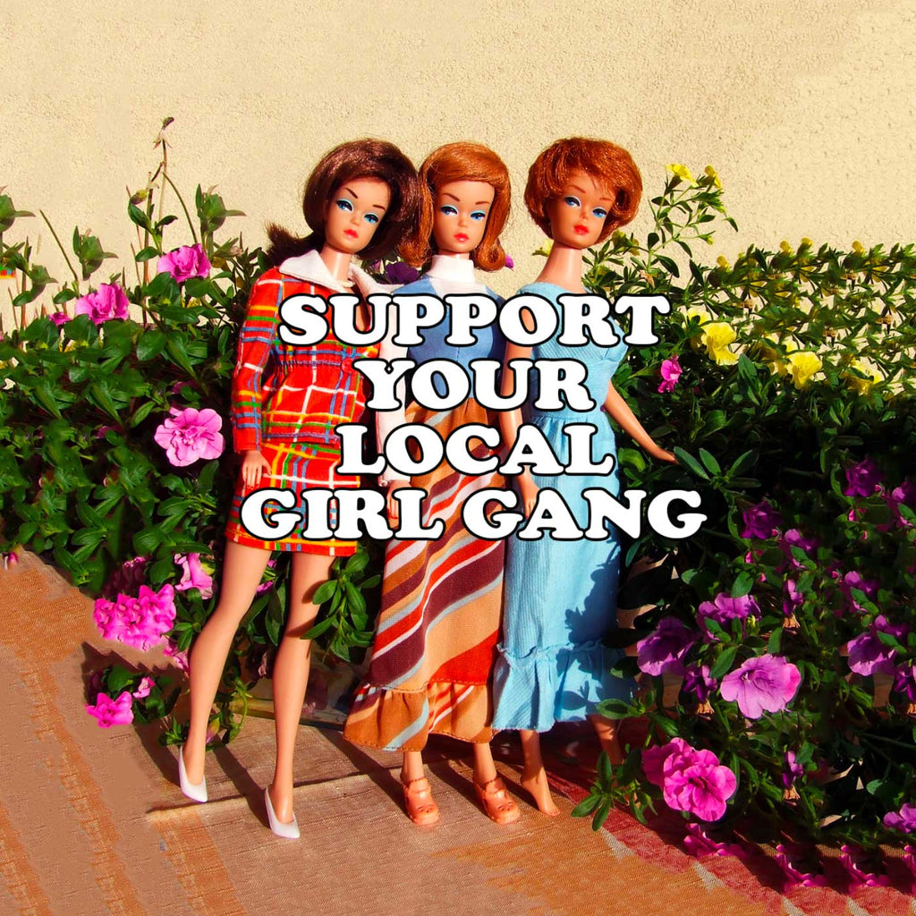 Image of vintage Barbie Dolls against a garden backdrop with the words Support Your Local Girl Gang across it
