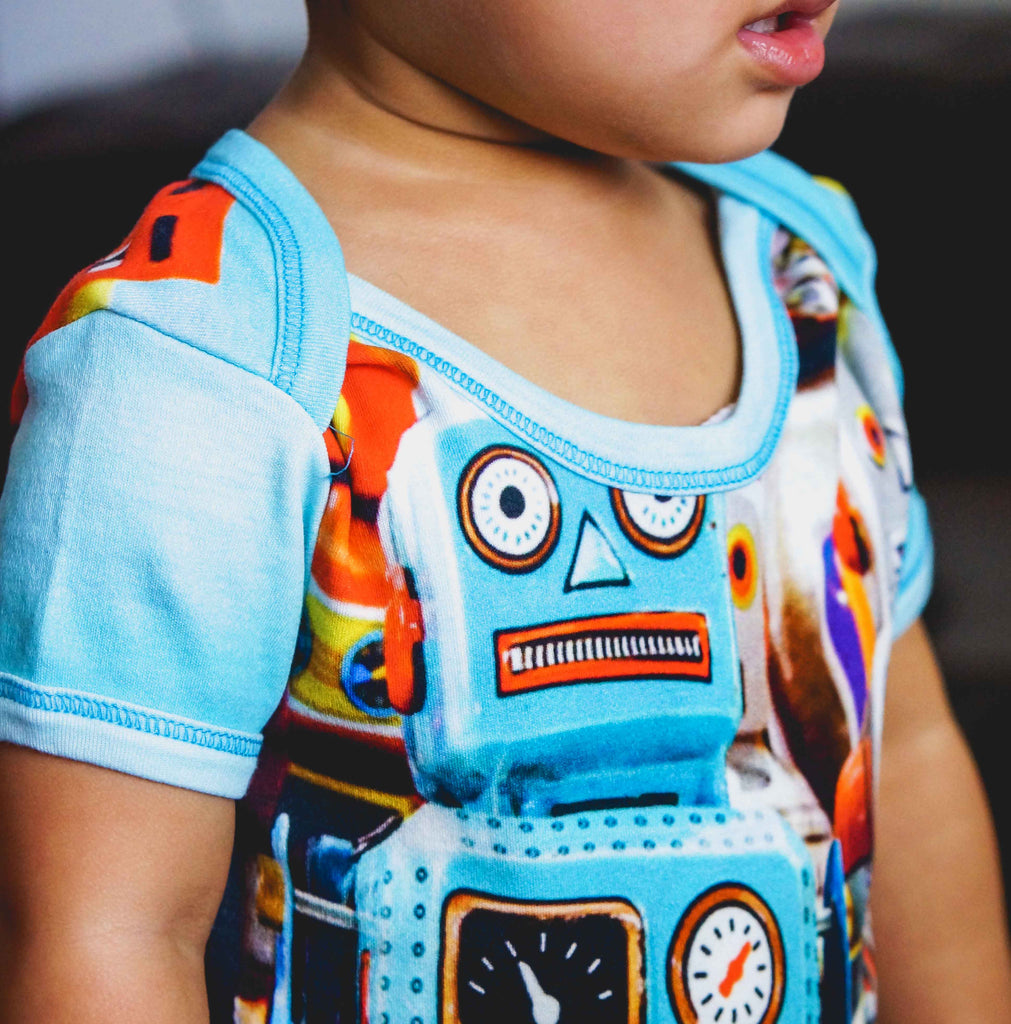 Baby wearing short sleeve bodysuit onesie printed with some colorful vintage tin toy robots