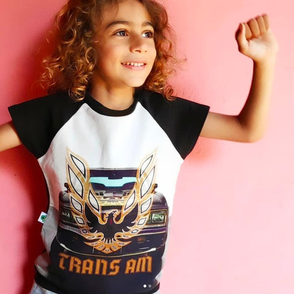 Child wearing a raglan cut-off tee with a front-end image of a classic Trans Am and the Firebird emblem and words TRANS AM superimposed on top