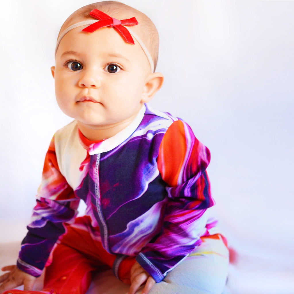 Baby wearing a long sleeve, full leg romper coverall with textural print of oil painting in purple, red, pink and cream