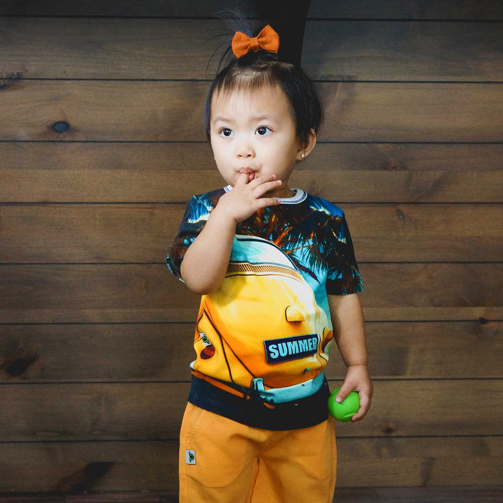 Toddler wearing a t-shirt printed with an image of a bright yellow VW Beetle or Bug, parked beach side, with a license plate that reads SUMMER