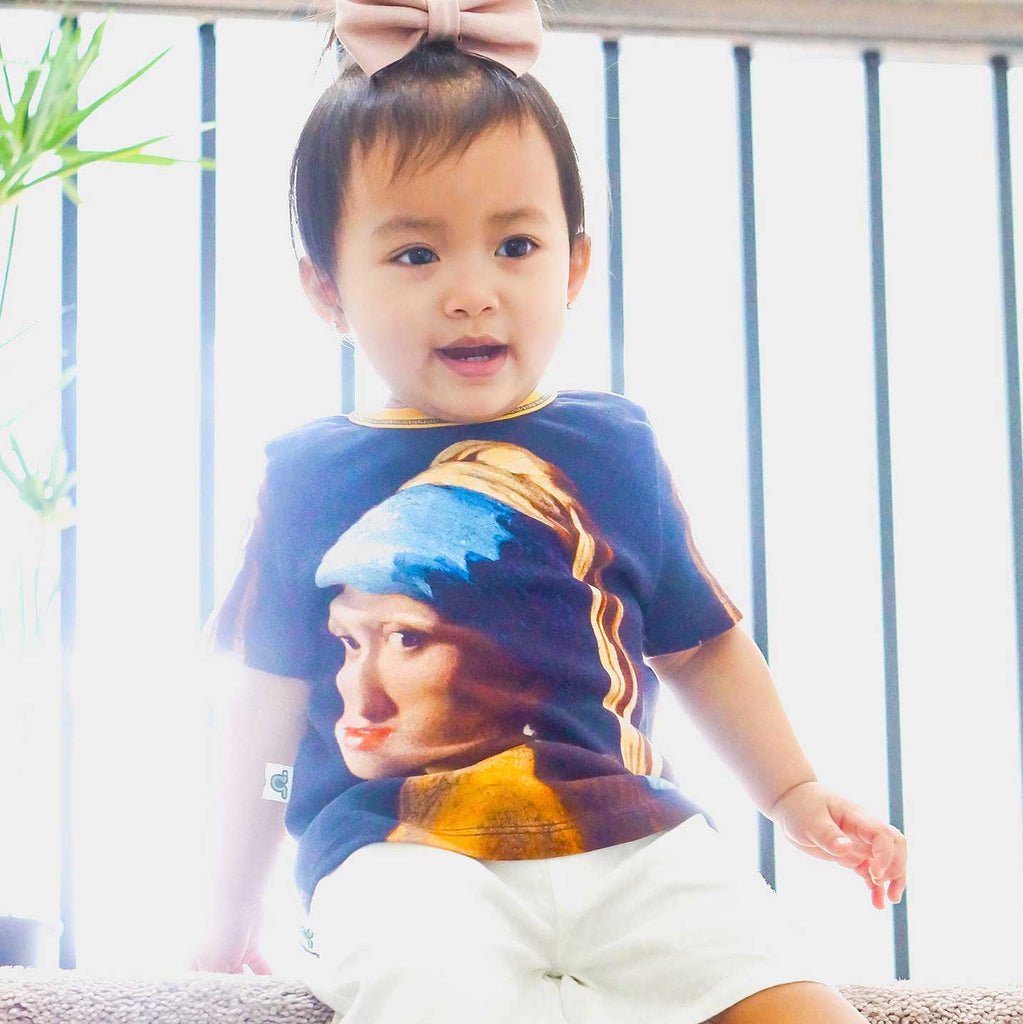 Toddler wearing a printed with an image of Johannes Vermeer's Girl with a Pearl Earring, an oil painting from the Dutch Godenmeer's Girl with a Pearl Earring, an oil painting from the Dutch Golden Age, dated 1665