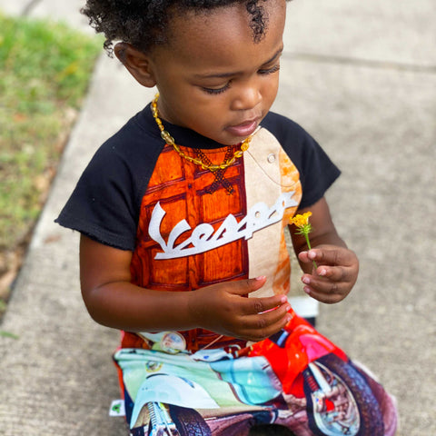 Toddler wearing a cut-off romper with image of two parked Vespas on a cobbled street