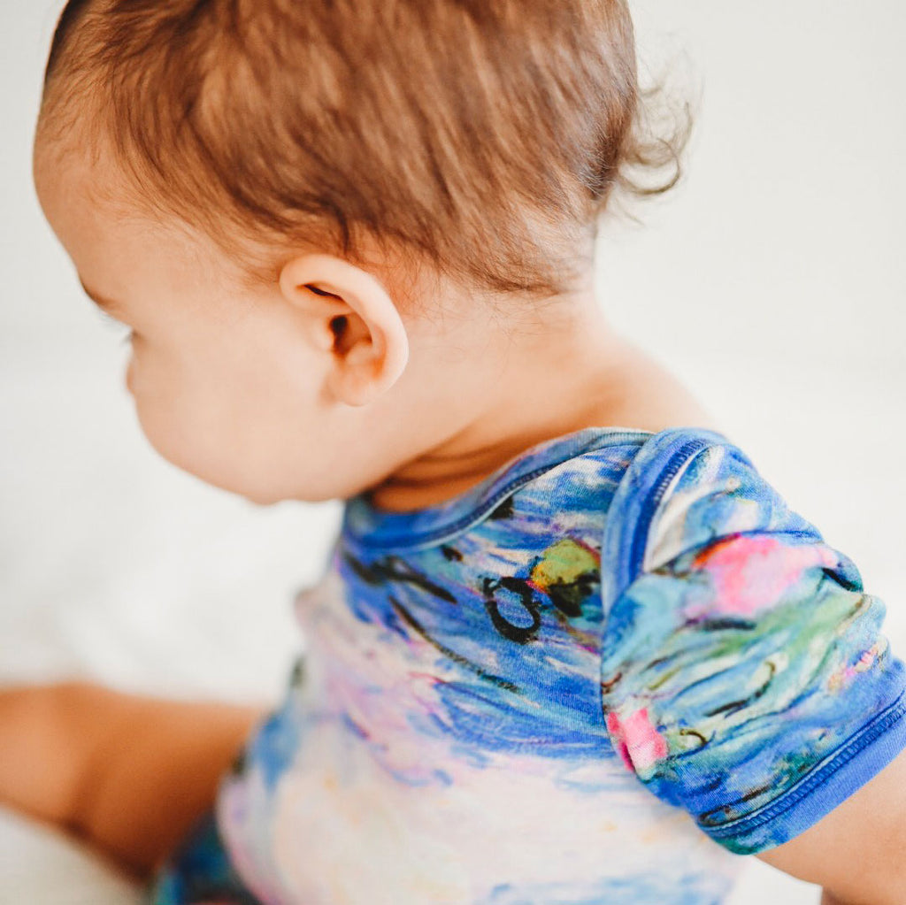 Baby wearing a short sleeve bodysuit onesie printed with an image of Claude Monet's painting Water Lilies from his series of 250 paintings