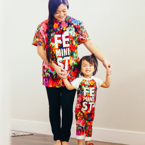 Mother and toddler wearing a raglan cut-off romper with an all-over print of multicoloured flowers and the text feMINIst across the chest