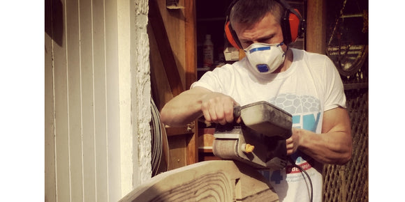 image of Jim sanding and shaping a surfboard chair