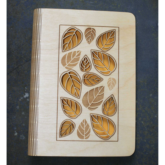 wooden note book cover with a leaves design