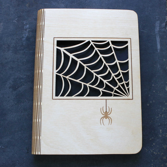wooden note book cover with a spider's web design