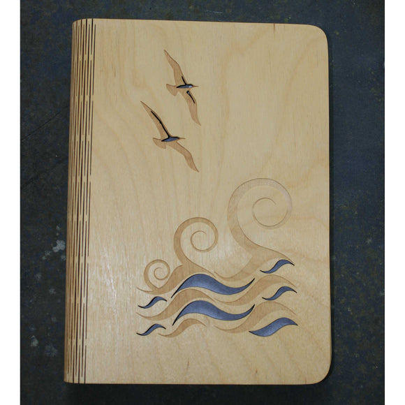 wooden note book cover with a wave and gulls seaside design