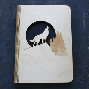 wooden note book cover with a wolf howling at the moon design