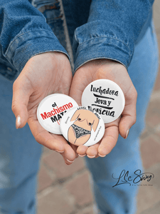 LSC Swag Model holding Amor Proprio Pin-Back 3-Pack Buttons