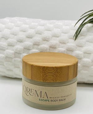 Qrema ESCAPE Body Balm - Qrema Paradise awaits as you escape with our Coconut Lime scented body balm. Wrap yourself in a delightful cocktail of aromas that are sure to take you far, far, away.  Escape has properties that help soothe, relax. It's uplifting and invigorating. It can help clear your mind and encourage mental energy.   Ingredients: shea butter, mineral oils, fragrance essential oil and natural powder.  *Contains Tree Nuts    2 oz container with a bamboo lid.