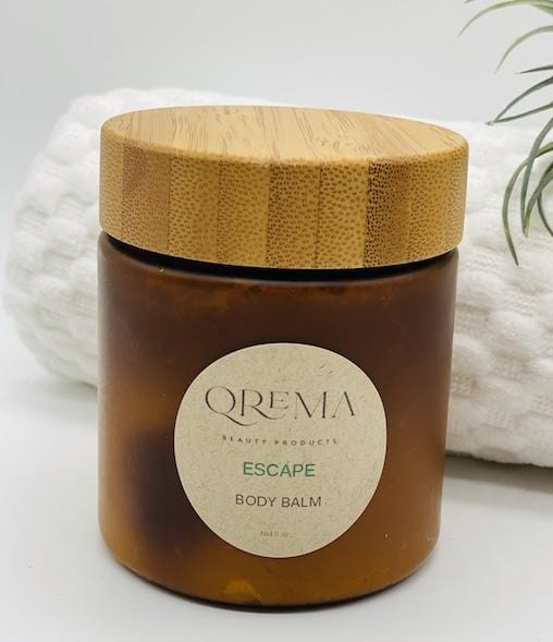 Qrema ESCAPE Body Balm - Qrema Paradise awaits as you escape with our Coconut Lime scented body balm. Wrap yourself in a delightful cocktail of aromas that are sure to take you far, far, away.  Escape has properties that help soothe, relax. It's uplifting and invigorating. It can help clear your mind and encourage mental energy.   Ingredients: shea butter, mineral oils, fragrance essential oil and natural powder.  *Contains Tree Nuts   8 oz bpa free container with bamboo lid.