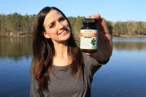 young happy woman showing bottle of probiotic