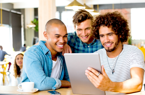 three male friends looking at laptop