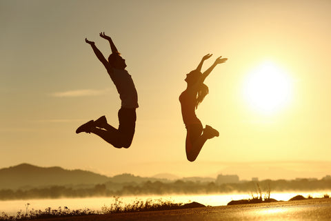 couple jumping towards the sun