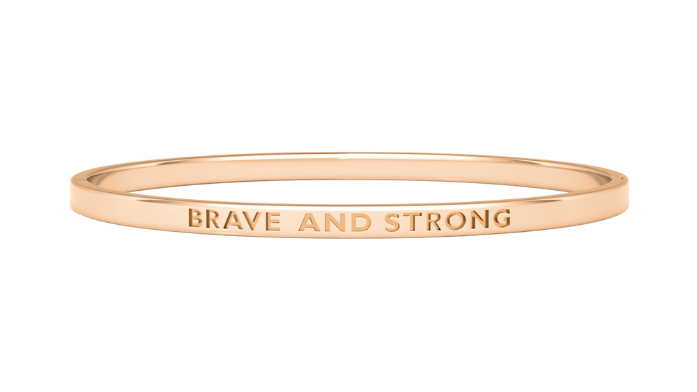 rose gold reminder bangle with brave and strong engraved on it