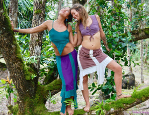 Two women stand in the jungle wearing mid length fairy skirts. One skirt is beige with white lace trim. The other is purple with a turquoise lace trim. Fairy women in the forest