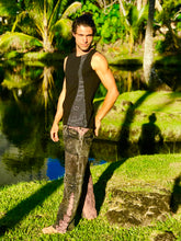 Load image into Gallery viewer, A man is standing wearing a 2 tone tank top black with a grey Shipibo print panel. He is standing on the grass in front of a pond and palm trees in hawaii