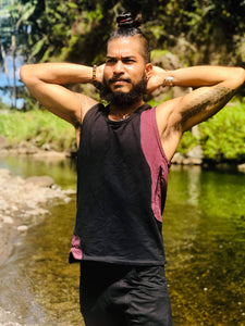 Man wearing a black and maroon 2 tone tank top stretches at a pond near the beach in hawaii