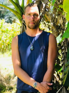 Man wearing soft navy blue Shipibo print tank top standing in front of banana trees in the sun in hawaii