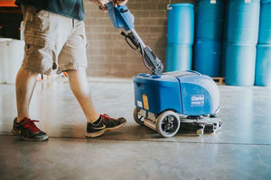 Man using automatic scrubber to clean concrete floor
