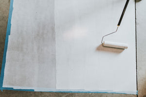 White paint being applied to concrete floor with a roller