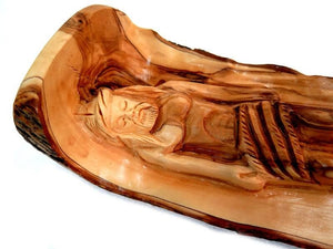 olive wood statue of Jesus lies on the Holy Anointing Stone