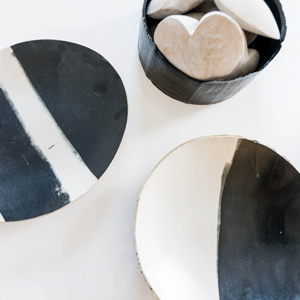 Black and white ceramic plates and candle vessel