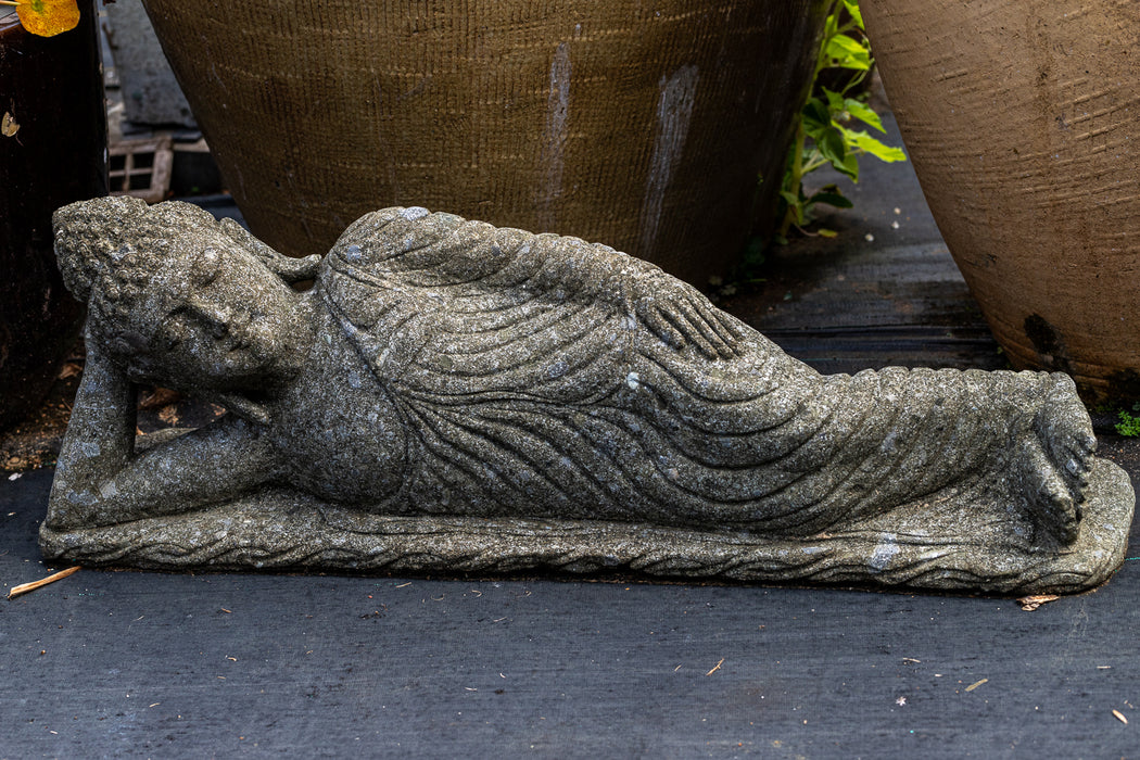 reclining buddha head on right arm draped robes hand carved stone statue