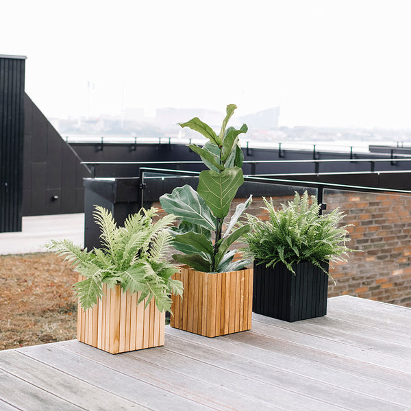 Three SQUARELY GrowOn wooden design planters on a terrace