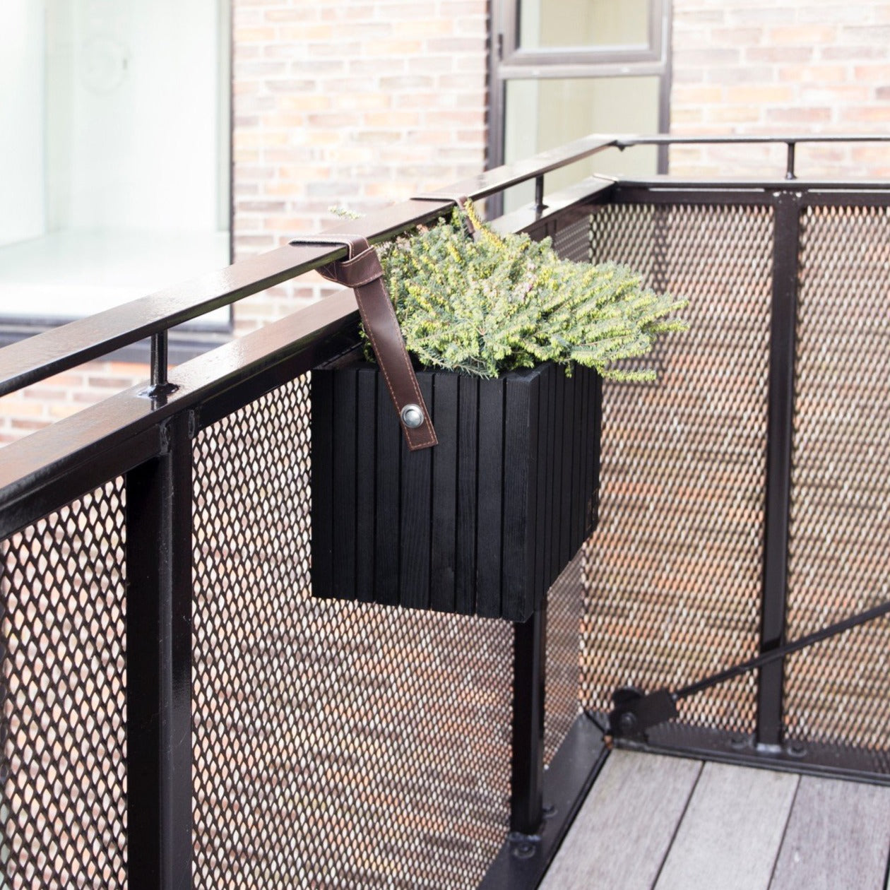 "SQUARELY's design planter ""GrowOn HoldOn Black Ash"" on a balcony . GrowOn HoldOn is SQUARELY's smaller, wooden, sustainable design planter with self-watering system."
