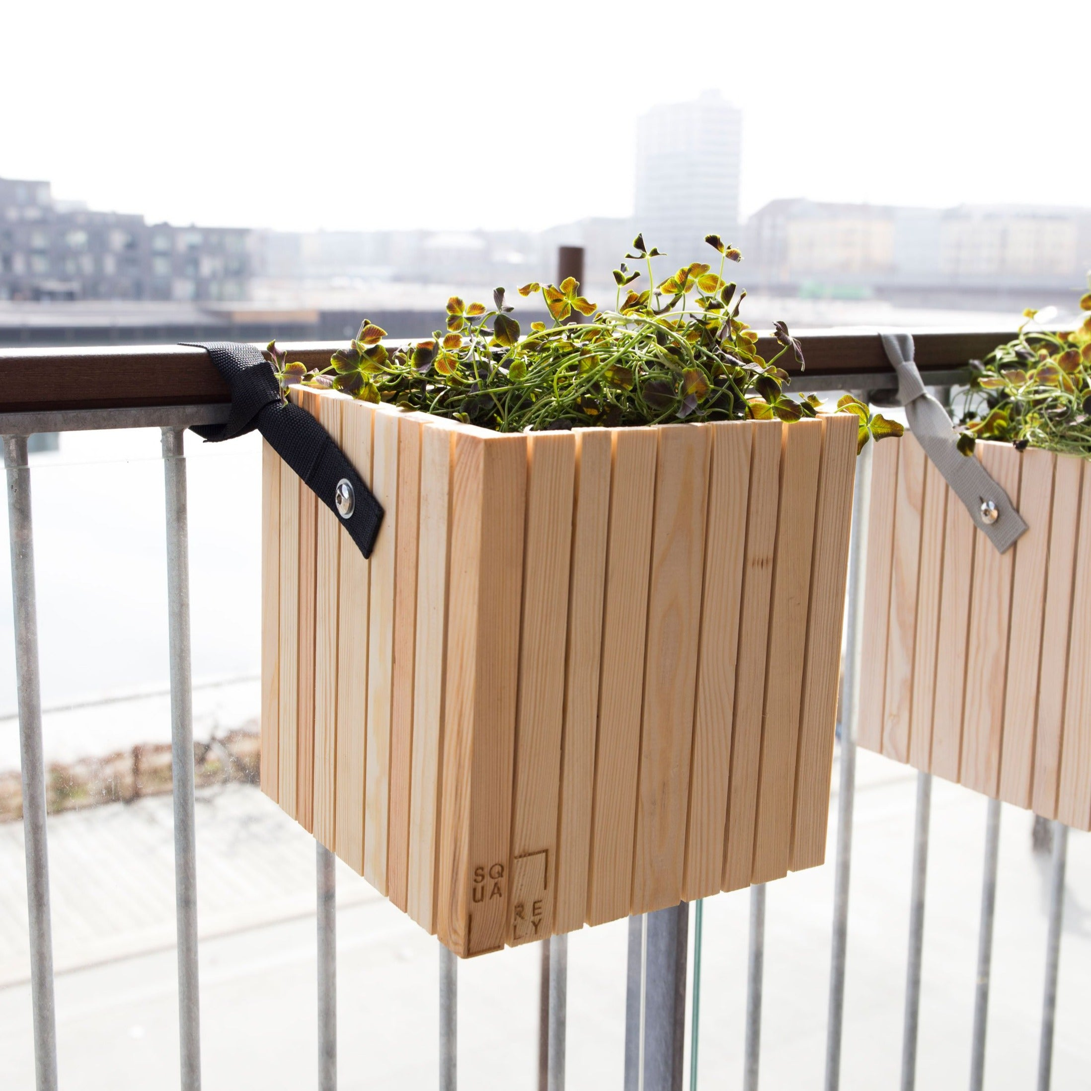 "SQUARELY's design planter ""GrowOn HoldOn Natural Ash"" on a balcony. GrowOn HoldOn is SQUARELY's smaller, wooden, sustainable design planter with self-watering system."