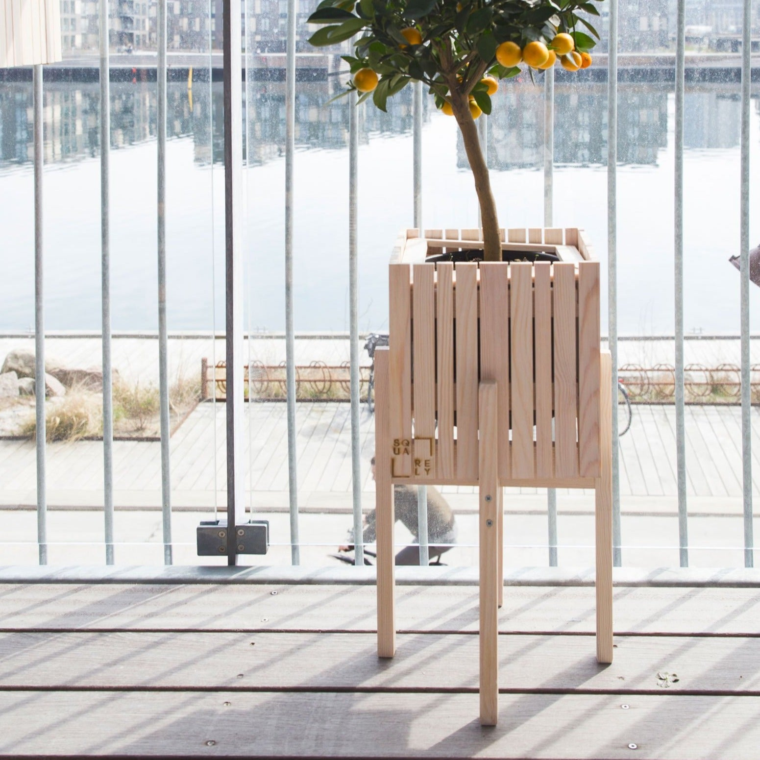 "SQUARELY's design planter with legs ""Grow On StandOn Natural Ash""on a terrace. GrowOn is SQUARELY's smaller, wooden, sustainable design planter with self-watering system."