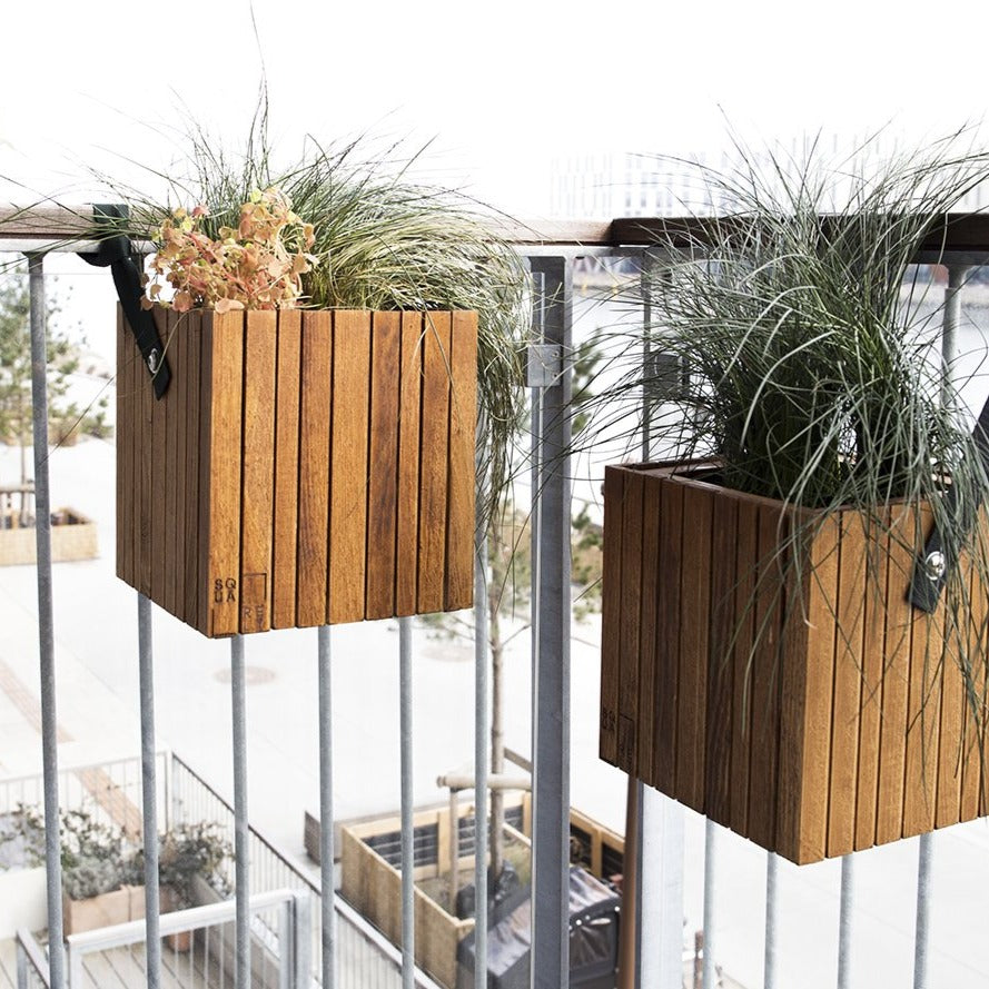 "SQUARELY's design planter ""GrowOn HoldOn DarkOak"" on a balcony. GrowOn HoldOn is SQUARELY's smaller, wooden, sustainable design planter with self-watering system."