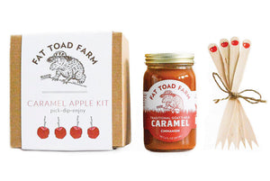 box with images of apples and toad next to jar of caramel and wooden sticks