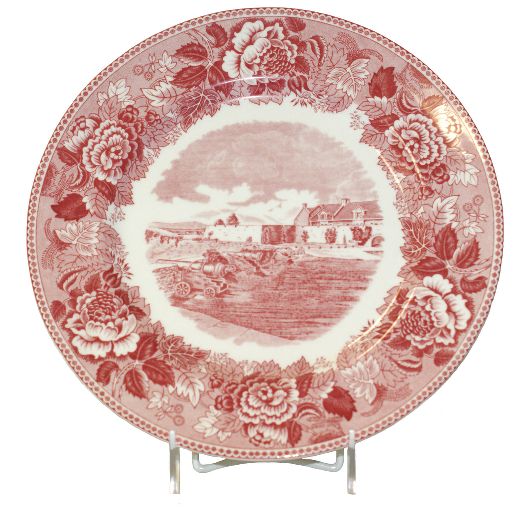 this red and white plate displays a floral design with a picture of the South Wall and South Barracks of Fort Ticonderoga centered in the middle