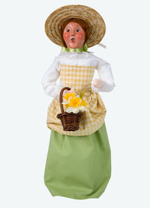 colonial figure with green dress, straw hat, and yellow flowers in a brown basket