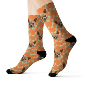 Feet with orange Customized / Personalized socks printed with a dog heads and bones.