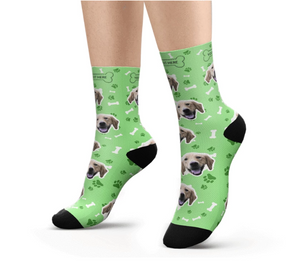 Feet with green Customized / Personalized socks printed with a dog heads and bones.
