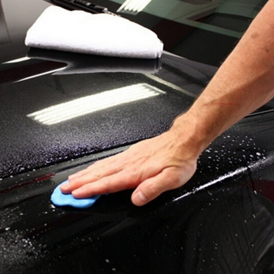 Mobile car detailing technician applying clay bar treatment