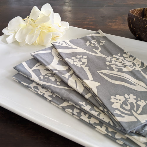 Picture of napkins with a white silhouette of Frangipani (Plumeria) buds and leaves on a cool gray background, pictured on a while porcelain plate decorated with white ginger and a coconut bowl on a dark table.