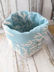 Reversible fabric basket in a light blue and cream colored starfish & coral design on a whitewashed wood background.