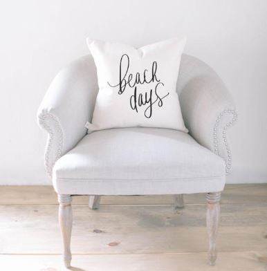 "18"" White throw pillow with ""beach days"" written in script on the front in black letters."
