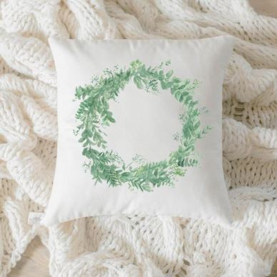 "18"" white throw pillow featuring a watercolor floral wreath print on the front"