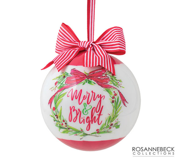 "Pink and white Christmas ornament featuring a green wreath and pink ""Merry and Bright"" lettering. Has a pink bow with white stripes on top."