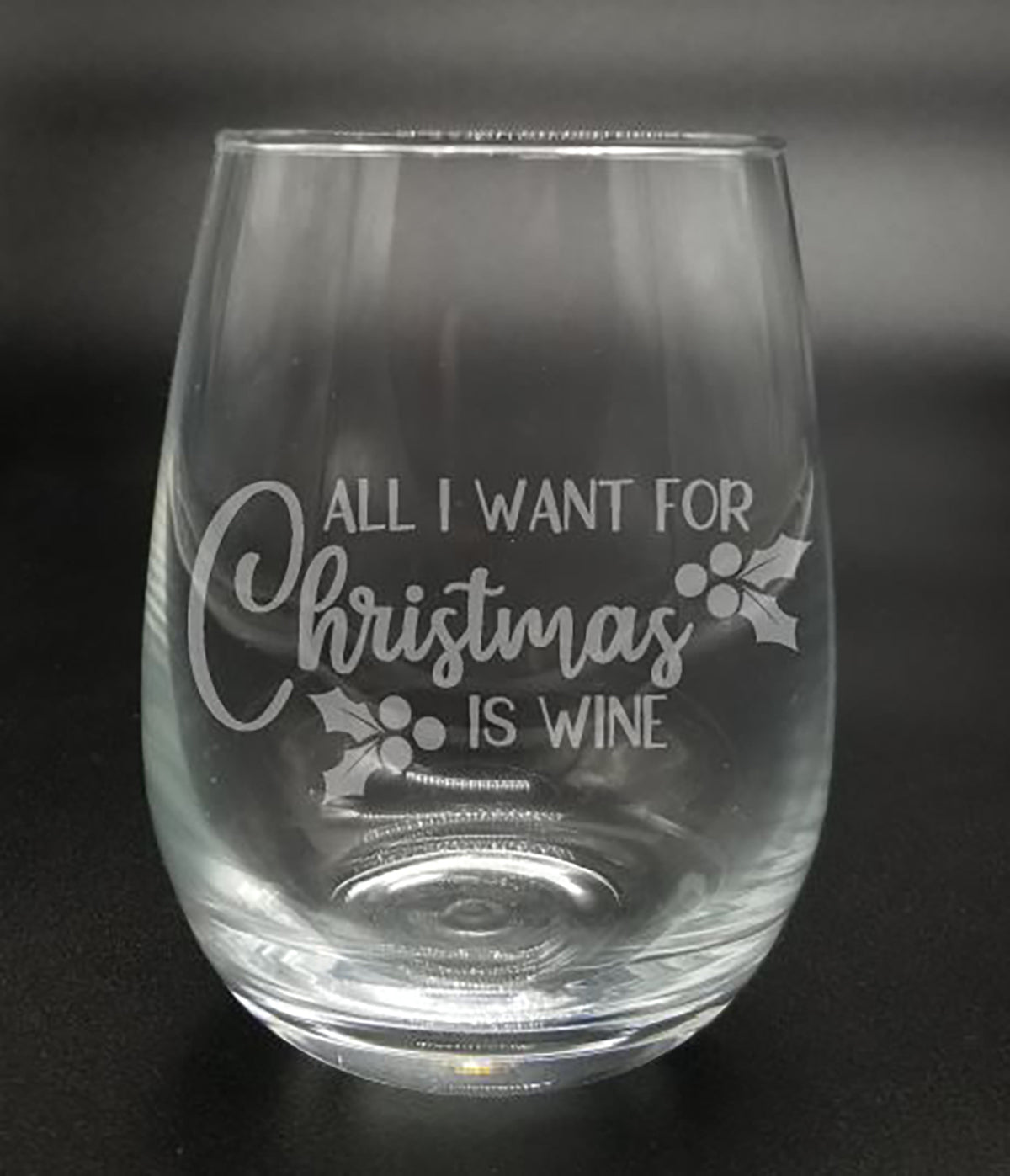 """All I want for Christmas is wine"" with holly leaves and berries etched on the front of either a stemless wine glass, or a stemmed wine glass"