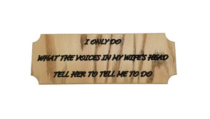 "Small wooden sign featuring the message ""I only do what the voices in my wife's head tell her to tell me to do"" in black letters"