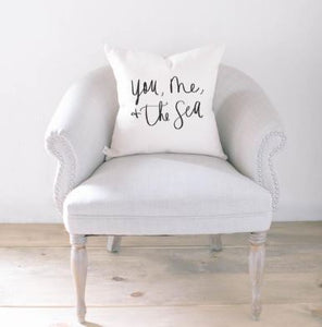 "18"" white throw pillow with ""you, me, and the sea"" printed in black script on the front"